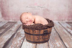 karine-majet-photographe-seance-photo-nouveau-ne-endormi-dans-un-baquet-en-bois